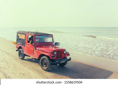 Arambol, Goa/India - 24.12.2018: Red rescue car with a loudspeaker and a yellow surf board on , on a sandy beach