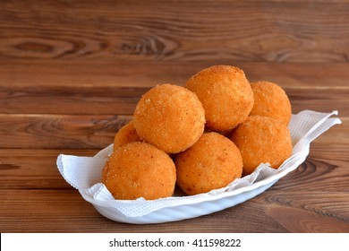 Arancini balls on a plate. Fried rice balls recipe. Brown wooden background