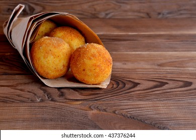 Arancini balls in paper on brown wooden background. Stuffed rice balls coated with bread crumbs and deep fried. Crispy and delicious snack, fast food