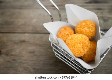 Arancini balls.potato croquette balls , Cheese Balls,Fried rice balls in paper on brown wooden background. Snack food.