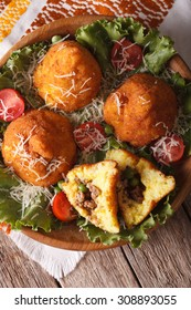 Arancini rice balls with meat and peas close-up on a plate. vertical top view
