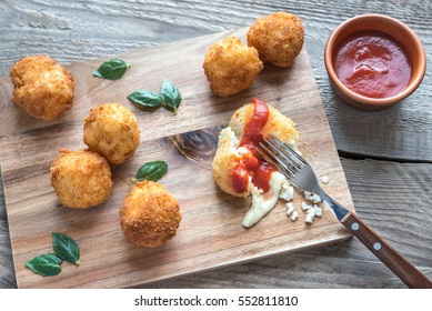 Arancini - rice balls with mozzarella on the wooden board