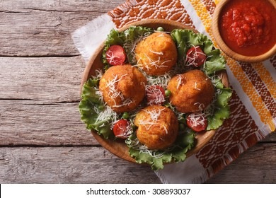 Arancini rice balls stuffed with meat and tomato sauce on a table. Horizontal top view