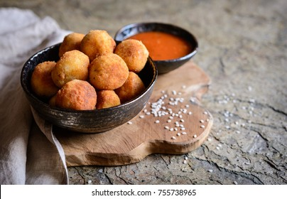 Arancini - traditional Italian deep fried rice balls with meat and cheese, served with tomato sauce