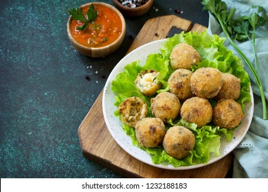 Arancini - traditional Italian Rice Balls with Mozzarella and Sun-dried tomatoes, served with tomato sauce. Copy space.