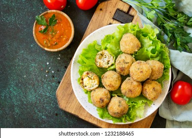 Arancini - traditional Italian Rice Balls with Mozzarella and Sun-dried tomatoes, served with tomato sauce. Top view flat lay background. Copy space.