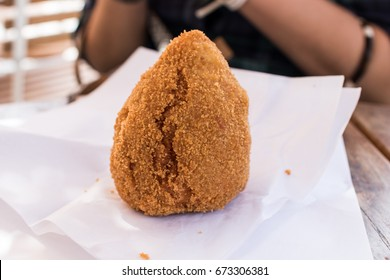 Arancino with ragù Sicilian gastronomic specialty, fried rice dumplings with meat sauce