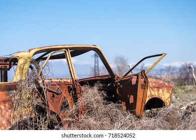 ARARAT, ARMENIA - APRIL 4, 2017: Abandoned and rusty wreckage of an yellow vintage Soviet Russian car in the middle of dry hay with scenic ice top mountains and clear blue sky on the background.