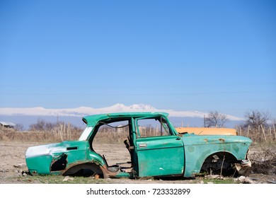 ARARAT PROVINCE, ARMENIA - APRIL 4, 2017: Abandoned and rusty wreck of an old green vintage Soviet Russian car with scenic snow-topped mountains on the background in rural Southern Armenia.