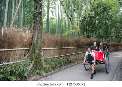 ARASHIYAMA, JAPAN - APRIL 4, 2013: Traditional hand pulled rickshaw in Sagano Bamboo Forest in Arashiyama at the outskirts of Kyoto. Arashiyama has been a popular destination since the 8th century.