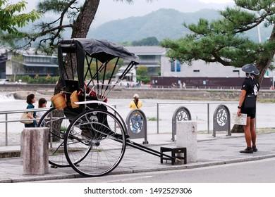 Arashiyama, Kyoto / Japan - Aug 18 2019: Rickshaw driver wearing a traditional Kasa hat waiting for tourist alongside a parked black rickshaw in Arashiyama district.