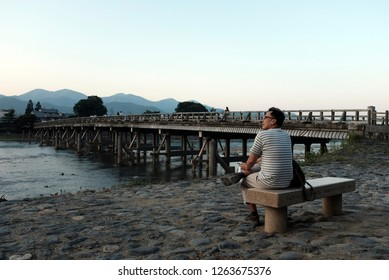 Arashiyama, Kyoto, Japan - July 2018 : An asian man sitting and enjoying a beautiful sunset scenery by Katsura river next to Togetsu-kyo bridge in Arashiyama, Kyoto, Japan.