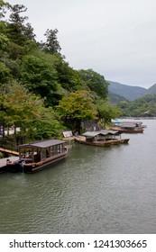 Arashiyama, Kyoto / Japan - June 21, 2018:  Boats docked along the shoreline of the Katsura River in Saga Arashiyama in the western hills of Kyoto.