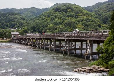 Arashiyama, Kyoto / Japan - June 21, 2018:  People cross the Togetsukyo Bridge that spans the Katsura River in Saga Arashiyama in the western hills of Kyoto.