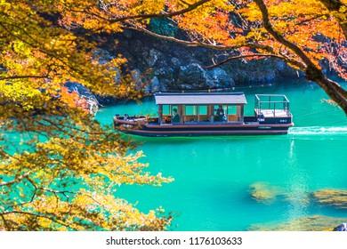 ARASHIYAMA, KYOTO, JAPAN - NOVEMBER 11, 2017: Unidentified boatman sail wooden boat to bring tourist people to enjoy autumn colors along katsura river to Arashiyama mountain area during fall season.