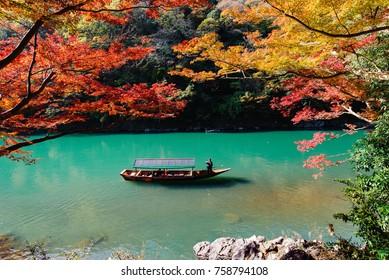 ARASHIYAMA, KYOTO, JAPAN - NOVEMBER 13, 2017: boat to bring tourist people to See autumn colors in Hozu-gawa river to Arashiyama mountain area, Kyoto, Japan