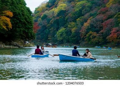 Arashiyama/Japan - November 11, 2015: Japanese tourists are riding boats on the lake of Arashiyama, Japan.