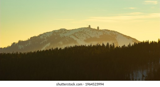 Großer Arber (Velký Javor) mountain with its iconic observatory in the colourful winter sunset. The peak located in a national park in Germany is covered in a haze. - Shutterstock ID 1964523994