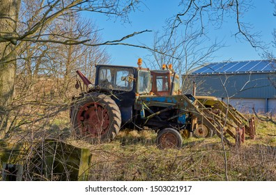 Arbilot, Scotland - 1st April 2018: A Pair of Old unused Tractors, parked up in light Woodland next to a Modern barn at a Farm at the Mains of Arbilot near to Arbroath, in Angus, Scotland.