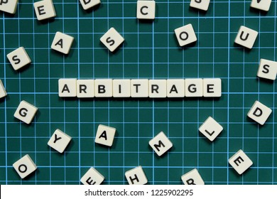 Arbitrage word made of square letter block on green square mat background.