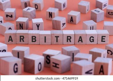 ARBITRAGE word on wooden cube isolated on orange background