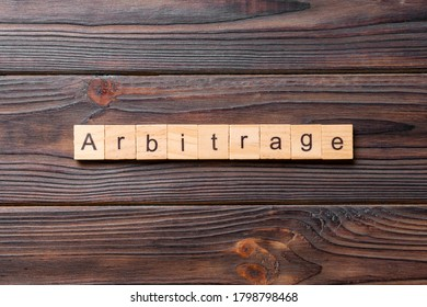 Arbitrage word written on wood block. Arbitrage text on cement table for your desing, concept.