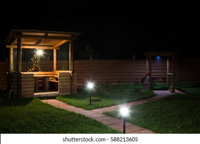 arbor and barbecue in the backyard at night