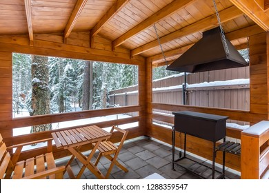 Arbor with barbecue on a snowy yard