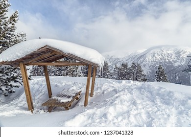 Arbor in the mountains in the snow among the firs. Wooden canopy among the snowdrifts in a frosty sunny day.