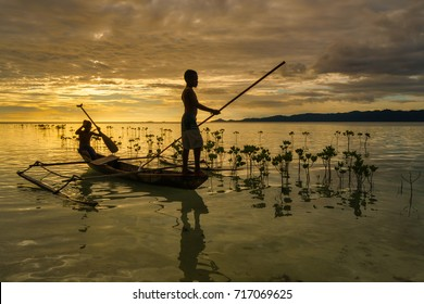 Arborek island, Raja Ampat, West Papua, Indonesia - August 7, 2017 : Boys fishing the traditional way with a long spear, almost sunset