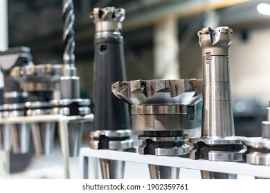Arbors with cutters and drills for a CNC machine on a rack, tools and equipment in a factory and an enterprise.