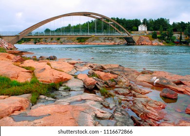 Arc bridge in  Bomarsund with small white museum house,typical  red rock ground and sea passage in cloudy summer day. Located in Aland Islands, Finland.