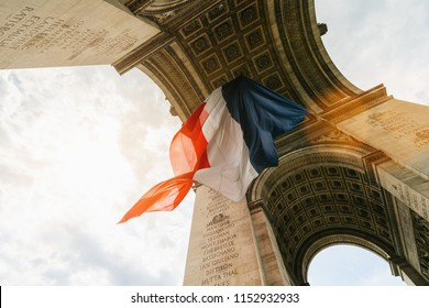 Arc de Triomphe with french flag during bastille day in paris, france
