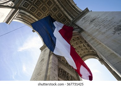 Arc de Triomphe with French flag hanging from vaulted ceiling inside the arch in Paris, France.