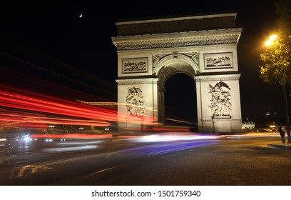 Arc de Triomphe, the half moon and streaks of light in red, white and blue of passing traffic at night in Paris, France