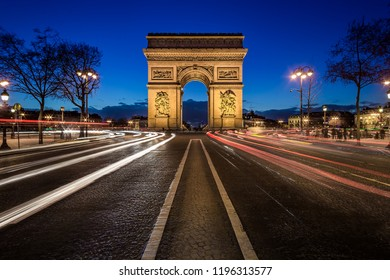 Arc de triomphe at night seen from the Champs-Elysées with a light trails of cars.