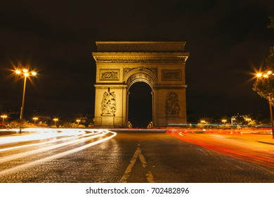 Arc de Triomphe at night with traffic