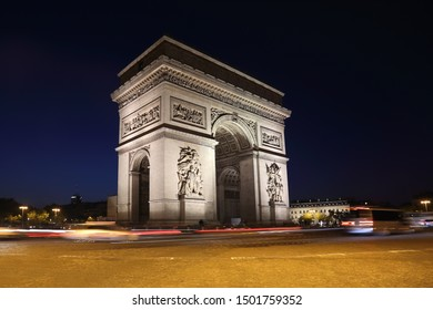 Arc de Triomphe and passing traffic at night in Paris, France