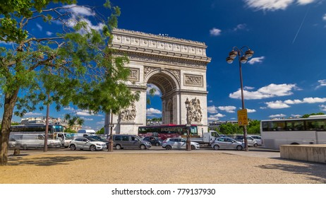 The Arc de Triomphe (Triumphal Arch of the Star) is one of the most famous monuments in Paris, standing at the western end of the Champs-Elyseees. Traffic on circle road. Blue