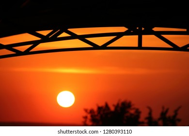 Arc polycarbonate canopy against a setting orange sun