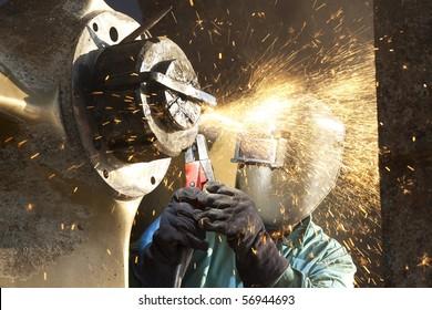 arc welder working on a tug boat wheel