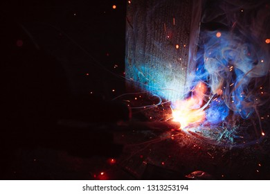 Arc welding. Welding of two sheets of metal by electrode in inert gases. Type MMA. A bright flash of light and a sheaf of sparks in a cloud of smoke. Miniature Universe. Free space for inscriptions.