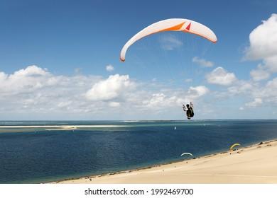 La baie d'Arcachon et le Banc d'Arguin vus depuis la dune de Pyla avec un parapente volant dans un ciel bleu et nuageux.