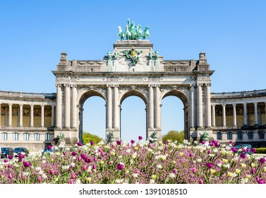 The arcade du Cinquantenaire, the triumphal arch erected by king Leopold II in the Cinquantenaire park in Brussels, Belgium, with a flowerbed in full bloom in the foreground against blue sky.