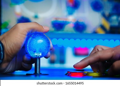 An arcade player using a joystick and pushing buttons to play a shoot 'em up genre type of video game.