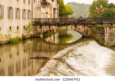 Arcades and dams on the old bridge over the river Salat as it passes through the village of Saint Girons. Ariege France