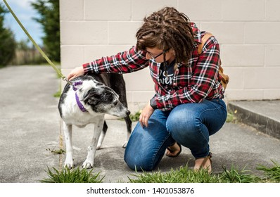 Arcata, California, US - 26th June, 2018: Young woman petting and comforting a nervous, old senior dog at an animal shelter