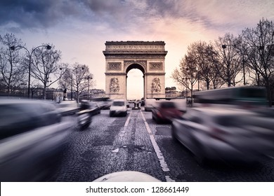 Arc-de-Triomphe on the Champs-Elysees in Paris, France, at sunset. Heavy traffic on the avenue.