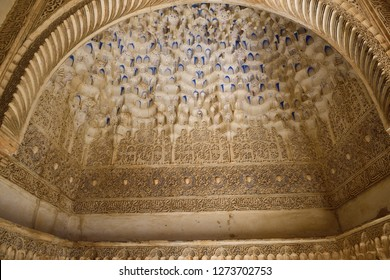 Arch with arabesque caligraphy and Mocarabe honeycomb designs in Comares Palace of Nasrid Alhambra Granada, Andalusia, Spain - April 29, 2015