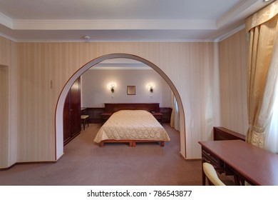 An arch in the bedroom with a big bed with a cover, lamps, a cabinet for clothes, a desk
